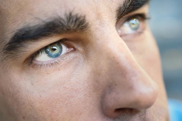 rosto aproximado de um home com olhos azuis