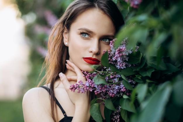 mulher posando ao lado de flores
