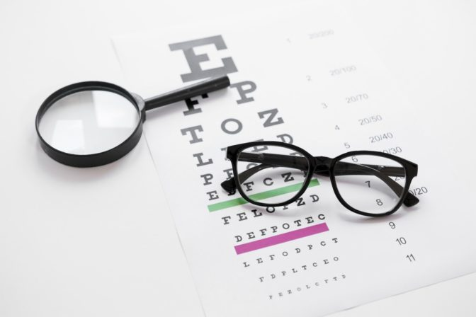 óculos e lupa em cima de tabela usada no teste de acuidade visual